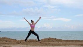 Ejercicio de la aptitud de la yoga de las prácticas de la muchacha cerca de la playa del océano en actitud del guerrero metrajes