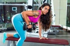 Ejercicio de la muchacha del contragolpe del tríceps de la pesa de gimnasia en el gimnasio Imágenes de archivo libres de regalías