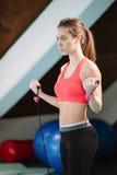 Ejercicio de la mujer joven con la cuerda de salto en el gimnasio Foto de archivo