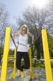 Ejercicio de la mujer joven en barras paralelas fotografía de archivo libre de regalías
