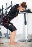 Ejercicio de la mujer joven en la electro máquina del estímulo fotos de archivo