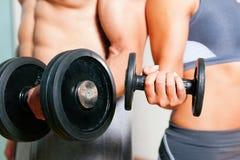 Ejercicio de la pesa de gimnasia en gimnasia Imagenes de archivo