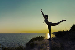 Ejercicio de la silueta de la muchacha gimnástico en la puesta del sol Imagenes de archivo