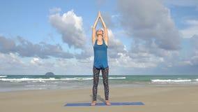 Ejercicio de la yoga de la balanza de la mujer joven en la playa delante del mar Concepto activo sano de la forma de vida metrajes