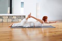 Ejercicio de la yoga en gimnasio y espejo de madera del piso Imágenes de archivo libres de regalías