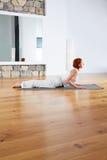 Ejercicio de la yoga en gimnasio y espejo de madera del piso Fotografía de archivo