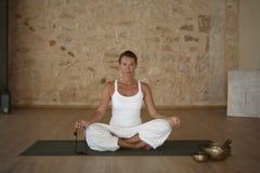 Ejercicio de la yoga interior en un cuarto Imagenes de archivo