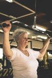 Ejercicio de trabajo de la mujer mayor activa en el gimnasio Fotos de archivo libres de regalías