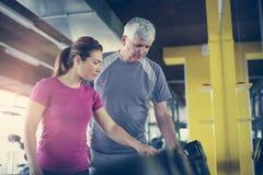 Ejercicio de trabajo del instructor con el hombre mayor en el gimnasio MA Imágenes de archivo libres de regalías