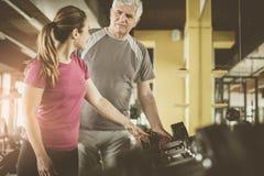 Ejercicio de trabajo del instructor con el hombre mayor en el gimnasio MA Fotografía de archivo libre de regalías
