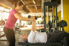 Ejercicio de trabajo del instructor con la mujer mayor en el gimnasio Imagen de archivo