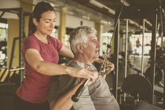 Ejercicio de trabajo del instructor personal con el hombre mayor en el gimnasio el PE imágenes de archivo libres de regalías