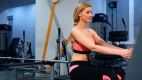 Ejercicio del entrenamiento cruzado de la mujer del entrenamiento cardiio usando el aparato de remar en gimnasio de la aptitud El almacen de video