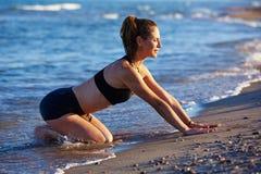 Ejercicio del entrenamiento de la yoga de Pilates al aire libre en la playa fotos de archivo