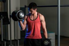 Ejercicio del hombre joven con pesas de gimnasia Imágenes de archivo libres de regalías