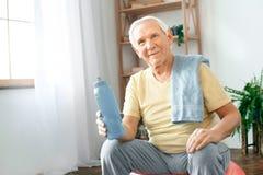 Ejercicio del hombre mayor en casa que se sienta en el agua potable del resto de la bola del ejercicio imagen de archivo libre de regalías