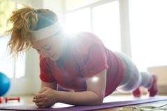 Ejercicio duro del tablón para la mujer obesa Imagen de archivo libre de regalías