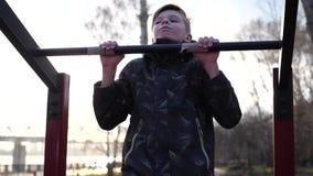 Ejercicio en el aire fresco Individuo fuerte joven que hace ejercicios en la barra Parque del oto?o almacen de video