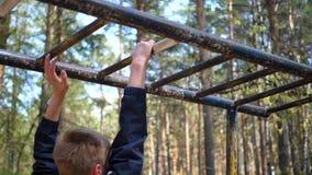 Ejercicio en el aire fresco Individuo fuerte joven que hace ejercicios en la barra Parque del oto?o almacen de metraje de vídeo