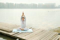 Ejercicio femenino de la yoga que hace al aire libre en el parque de la ciudad Fotos de archivo