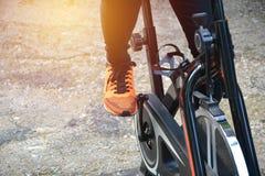 Ejercicio femenino en la bicicleta para ejercitar y el lifestyl sano imagenes de archivo