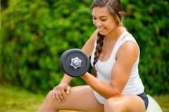 Ejercicio femenino expectante con pesas de gimnasia para fortalecer los brazos adentro imágenes de archivo libres de regalías