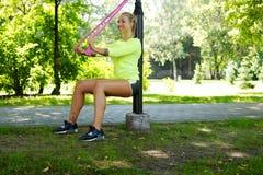 Ejercicio femenino rubio atlético con las correas del trx de la aptitud Foto de archivo libre de regalías