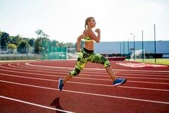 Ejercicio hermoso de la mujer joven que activa y que corre en pista atlética en estadio Fotografía de archivo