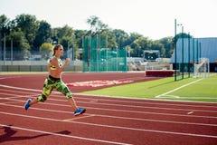 Ejercicio hermoso de la mujer joven que activa y que corre en pista atlética en estadio Foto de archivo