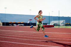 Ejercicio hermoso de la mujer joven que activa y que corre en pista atlética en estadio Foto de archivo libre de regalías