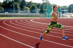 Ejercicio hermoso de la mujer joven que activa y que corre en pista atlética en estadio Imagenes de archivo