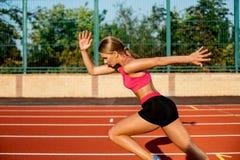 Ejercicio hermoso de la mujer joven de la vista lateral que activa y que corre en pista atlética en estadio Fotos de archivo