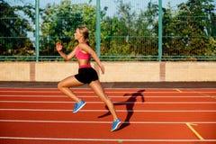 Ejercicio hermoso de la mujer joven de la vista lateral que activa y que corre en pista atlética en estadio Foto de archivo libre de regalías