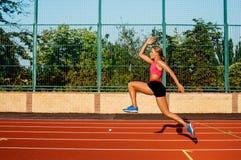 Ejercicio hermoso de la mujer joven de la vista lateral que activa y que corre en pista atlética en estadio Fotografía de archivo