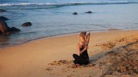 Ejercicio hermoso de la yoga de las prácticas de la muchacha en la playa amarilla de la arena almacen de video
