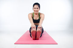 Ejercicio interior de la mujer hermosa usando la estera rosada de la yoga Imagen de archivo