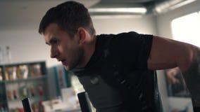 Ejercicio masculino en barras desiguales en gimnasio, cierre del atleta para arriba almacen de video