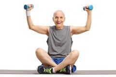 Ejercicio mayor con pequeñas pesas de gimnasia en una estera del ejercicio imagenes de archivo