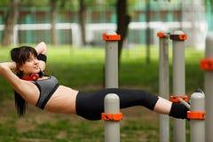 Ejercicio moreno atlético para los músculos abdominales en barras del gimnasio Fotografía de archivo