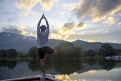 Ejercicio pacífico de la yoga de las mujeres delante de la charca Fotos de archivo libres de regalías