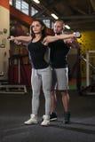 Ejercicio personal de Showing Young Woman del instructor para los hombros foto de archivo libre de regalías