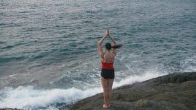 Ejercicio practicante de la aptitud de la yoga de la mujer tranquila en la playa rocosa delante del océano tempestuoso almacen de metraje de vídeo