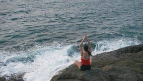 Ejercicio practicante de la aptitud de la yoga de la mujer tranquila en la playa rocosa delante del océano tempestuoso almacen de video