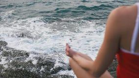 Ejercicio practicante de la aptitud de la yoga de la mujer tranquila en la playa rocosa delante del océano tempestuoso metrajes