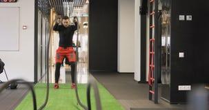 Ejercicio practicante de la cuerda de la batalla del hombre adulto joven durante un entrenamiento del crossfit en el gimnasio almacen de video