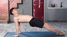 Ejercicio practicante de la yoga del hombre flexible fuerte que relaja y que hace vista lateral de respiración almacen de video