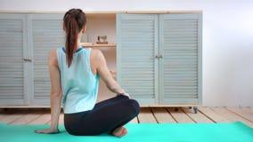 Ejercicio practicante de la yoga de la mujer joven de la flexibilidad del tiro lleno que se sienta en actitud del loto del asana almacen de video