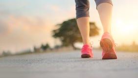 Ejercicio que camina de la mujer del atleta en el camino rural en backgroun de la puesta del sol fotografía de archivo