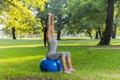 Ejercicio sano de la mujer joven de la aptitud con la bola de Pilates al aire libre Fotos de archivo