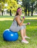 Ejercicio sonriente sano de la mujer joven de la aptitud en la bola de Pilates Imágenes de archivo libres de regalías
